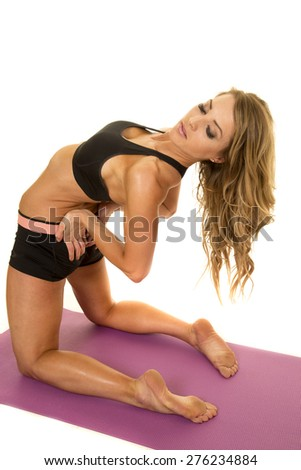 A fit woman leaning back, stretching out her back - stock photo