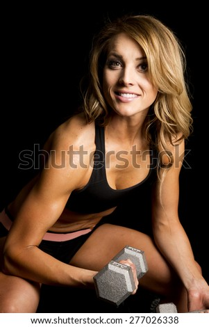 A fit woman sitting on a bench, and doing an arm curl.