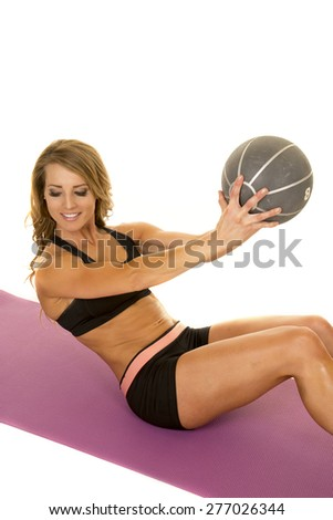 A fit woman sitting on her mat, with a smile working out with her medicine ball. - stock photo