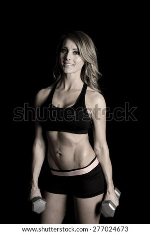 A fit woman with a smile, holding on to her weights.