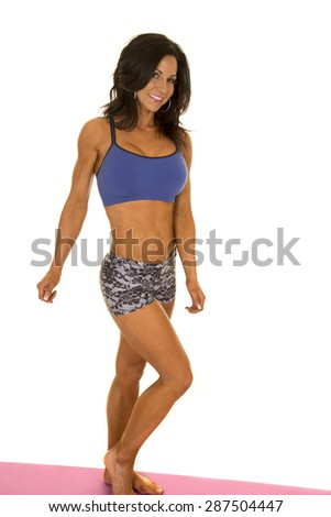 a fit woman with a smile posing her body.
