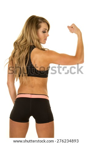 A fit woman with her back to the camera looking at her muscles.