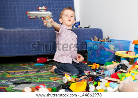 A five year old child playing in his room with a lot of toys around him. A five year old boy pointing at something/someone with his toy gun - stock photo