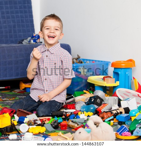 A five year old child playing in his room with a lot of toys around him. A five year old boy holding something in his small fist and laughing