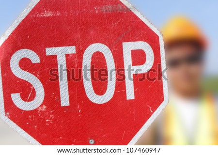 A flag person holds up a stop sign for on-coming motorists. /Flag Person Holds Stop Sign/A person is assigned to control traffic in a construction area.