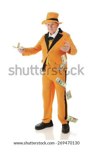 A flamboyant senior adult in a bright orange tuxedo and hat, carelessly offering money and dropping big bills.  On a white background. - stock photo