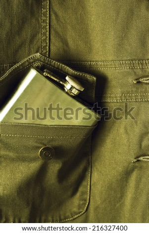 A flask sticking out of a jacket pocket. - stock photo