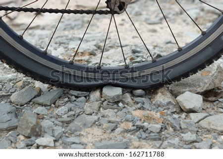 a flat tire on rocks - stock photo
