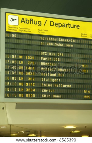 a flight announcement shows time of departure on a screen