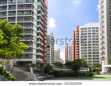 A flight of stairs leading to orange color residential estate with a basketball court- Singapore - stock photo