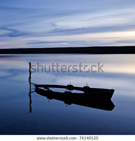 A flooded boat at twilight on the Fleet Lagoon near Weymouth, Dorset, UK