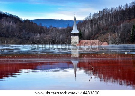 A flooded church in a toxic red lake. Water polluting by a copper mine - stock photo
