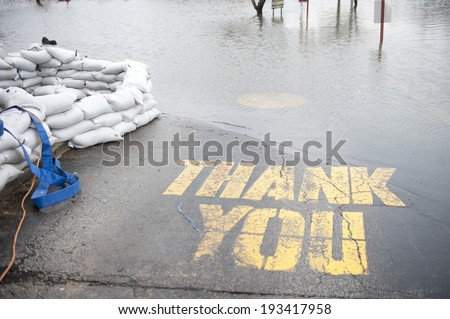A flooded thrive through sign with a thank you written on the ground and sandbags surrounding the restaurant. - stock photo
