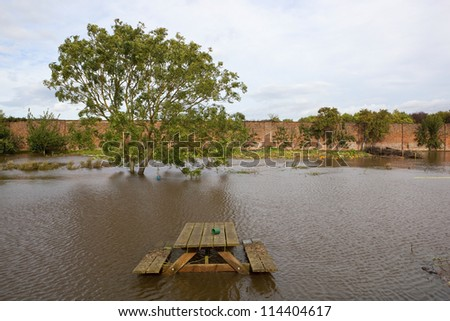 a flooded walled garden in autumn with a submerged picnic bench with trees and vegetation under a cloudy sky