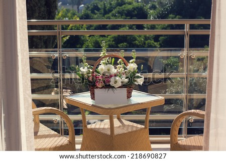 A floral basket on the glass terrace table