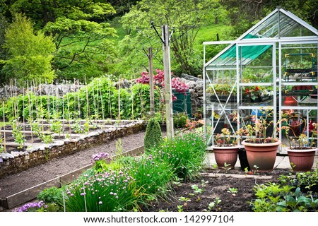 A flourishing vegetable garden and greenhouse in rural England - stock photo