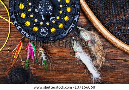 A fly fishing reel with flies and a landing net on a wet wooden background - stock photo