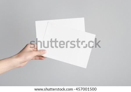 A5 Flyer / Invitation Mock-Up - Male hands holding blank flyers on a gray background.