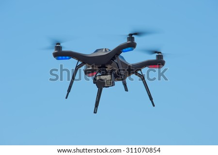 A flying drone armed with camera - stock photo
