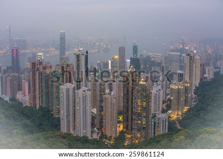A foggy Hong Kong and Kowloon skyline with skyscrapers before sunset, as seen from Victoria Peak. The apartment lights across the city are on and the small bay looks quiet.