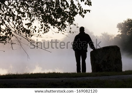 A foggy morning and quite lake makes for an inspirational location for this adult male to contemplate life's challenges and rewards in a quiet setting. - stock photo