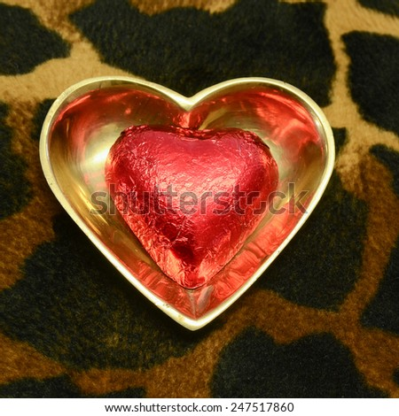 A foil wrapped red chocolate in a heart shaped brass dish on a faux animal skin surface - stock photo