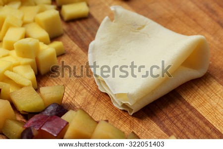 A folded Crepe next to mango and plum