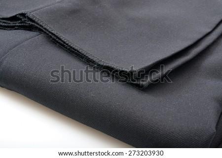 A folded pair of un-hemmed mens dress slacks closeup - stock photo