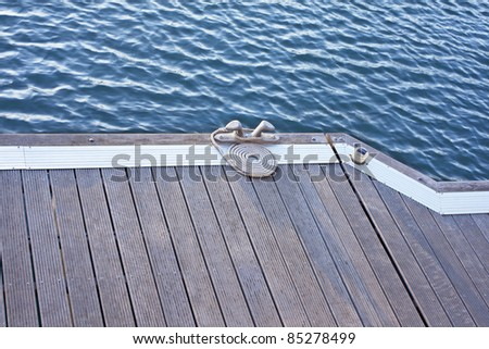 A folded spiral mooring rope with a end knot around a cleat on a wooden pier - stock photo