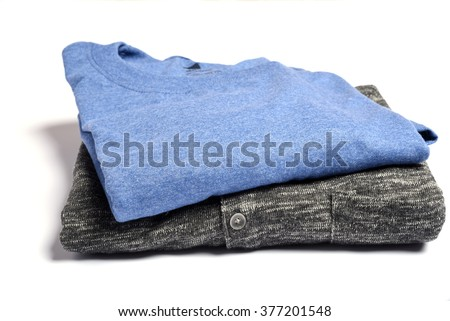 A folded t-shirt and sweater on a white table - stock photo