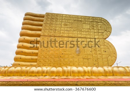 A foot print big statue of reclining buddha image in the temple. - stock photo