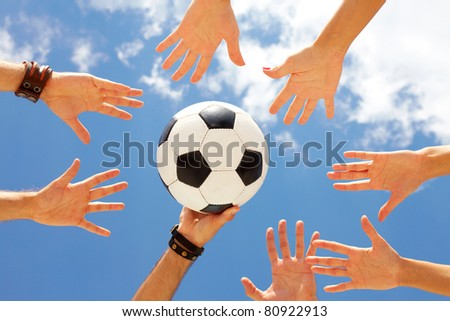 A football ball in circle of hands - stock photo