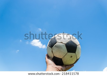 A football ball in  hands on blue sky background. - stock photo