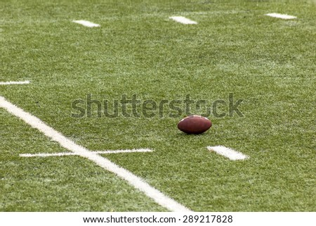 A football ball in the field in the scrimmage line