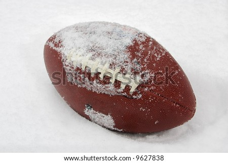 a football covered with snow and laying in the snow - stock photo