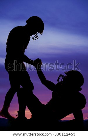 A football player showing teamwork, helping another player out.