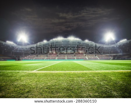a football stadium with fans in the evening - stock photo