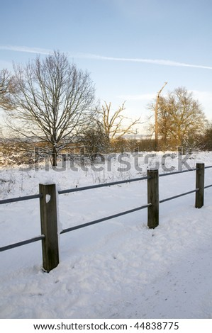 A footpath covered in snow with a fence - stock photo