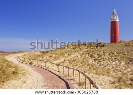 A footpath leading towards the lighthouse of the island of Texel in The Netherlands on a sunny day. - stock photo