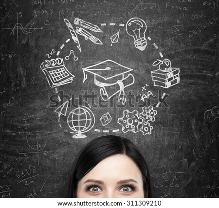 A forehead of the brunette lady who thinks about studying and graduation. Educational icons are drawn on the black chalkboard. - stock photo