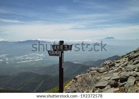 A foreign sign overlooking a view of mountains. - stock photo