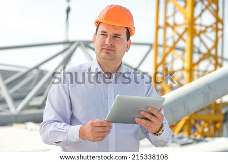 A foreman with digital tablet at the construction supervising the project. - stock photo