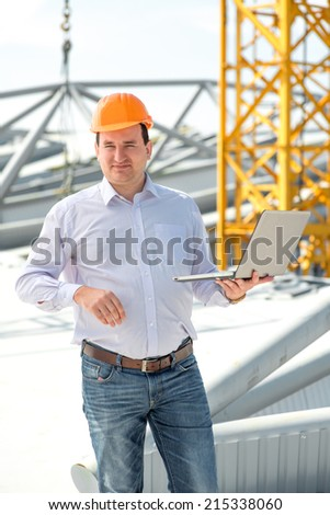 A foreman with laptop at the construction supervising the project. - stock photo