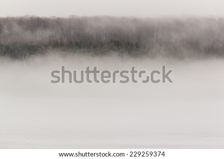 A forested island shrouded in fog.  Round Island, MI, USA. - stock photo