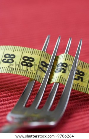 a fork and a measure tape, conceptual loose weight (soft and selective focus)