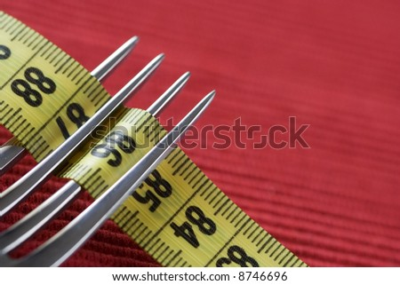 a fork and a mesure tape, conceptual loose weight (soft and selective focus) - stock photo