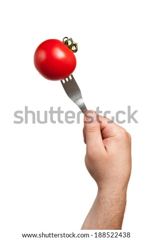 A fork stucked in a tomato hold by the cook's hand and everything on a white background
