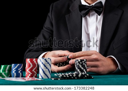 A formal dressed man counting his casino chips