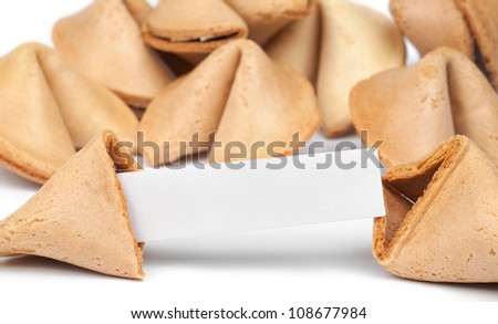 A fortune cookie with fortune paper in front of a pile of other cookies isolated on white. - stock photo