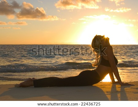 A forty year old woman doing yoga at sunrise on the beach in Hawaii